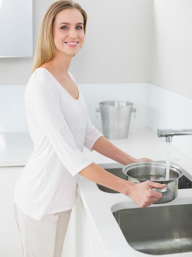 Pentola di riempimento della donna splendida felice con acqua immagini stock libere da diritti