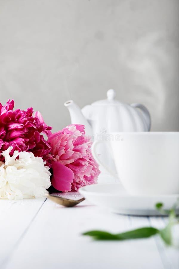 Peonías hermosas frescas de las flores y una taza blanca de cerámica con el té para el desayuno foto de archivo