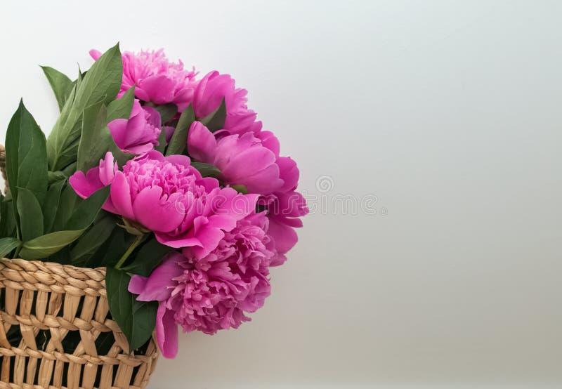 Peonías rosadas en cesta de la paja cerca de la pared blanca foto de archivo libre de regalías