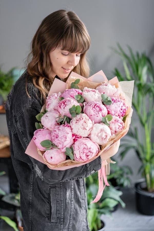 Peonie rosa in mani della donna Bello fiore della peonia per il catalogo o il deposito online Concetto floreale del negozio Bello fotografia stock libera da diritti