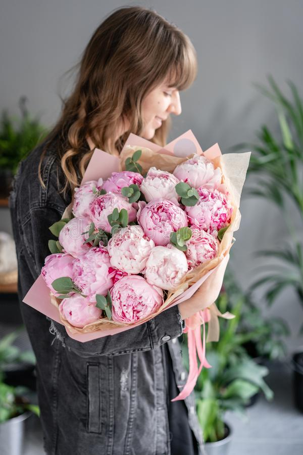 Peonie rosa in mani della donna Bello fiore della peonia per il catalogo o il deposito online Concetto floreale del negozio Bello fotografia stock