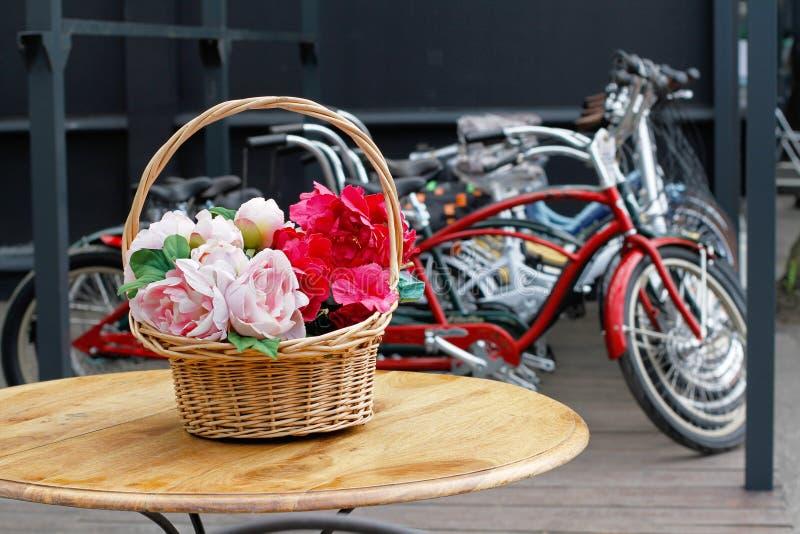 Peonie w koszykowej pozyci na stole na tle bicykle obrazy stock