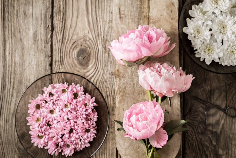 Peonies και πιάτα με τα λουλούδια στην ξύλινη άποψη επιτραπέζιων κορυφών στοκ φωτογραφίες