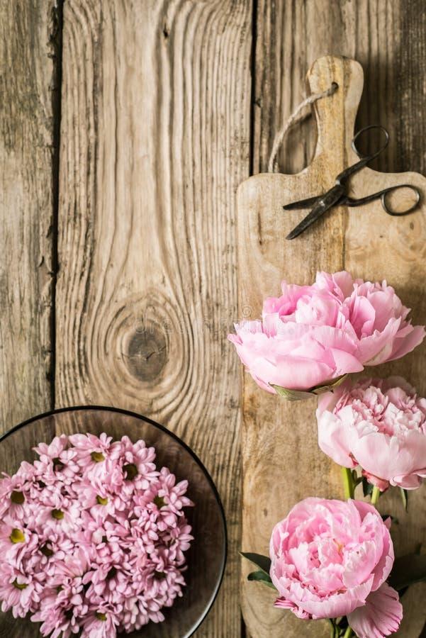 Peonies και πιάτο με τα λουλούδια στην ξύλινη επιτραπέζια κατακόρυφο στοκ εικόνα με δικαίωμα ελεύθερης χρήσης