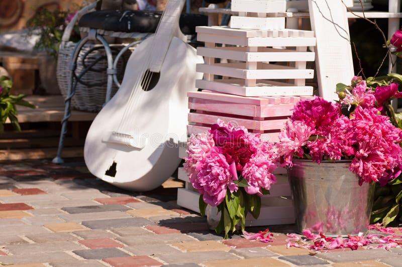 Peonies στον κάδο και μια άσπρη κιθάρα στοκ φωτογραφία