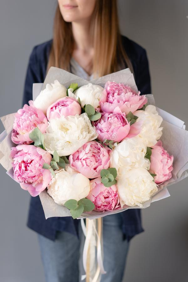 Pink and white peonies in womans hands. Beautiful peony flower for catalog or online store. Floral shop concept stock images