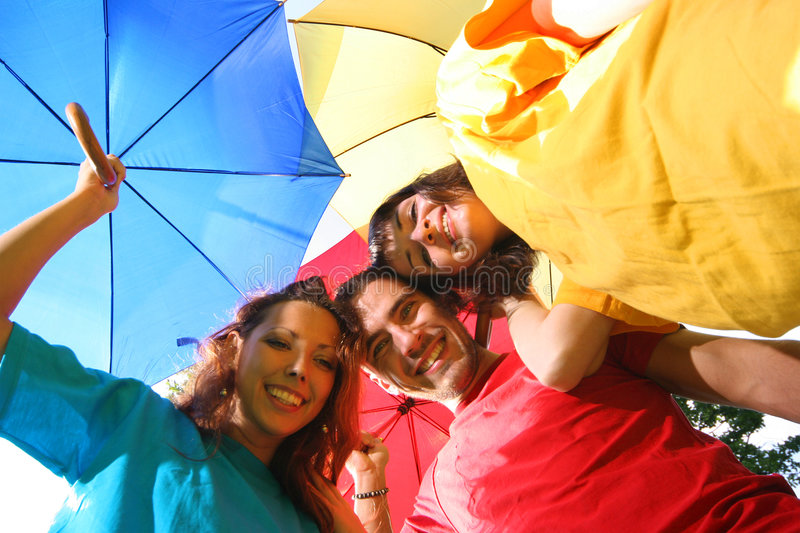 People. Funny colorful friends with umbrellas royalty free stock images