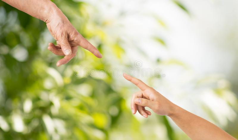 Close up of senior and young woman hands. People, age and body parts concept - close up of senior and young woman hands pointing finger over green natural stock photography