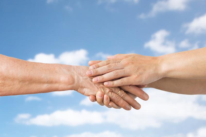 Close up of senior and young woman holding hands. People, age and charity concept - close up of senior and young woman holding hands over blue sky and clouds stock photos