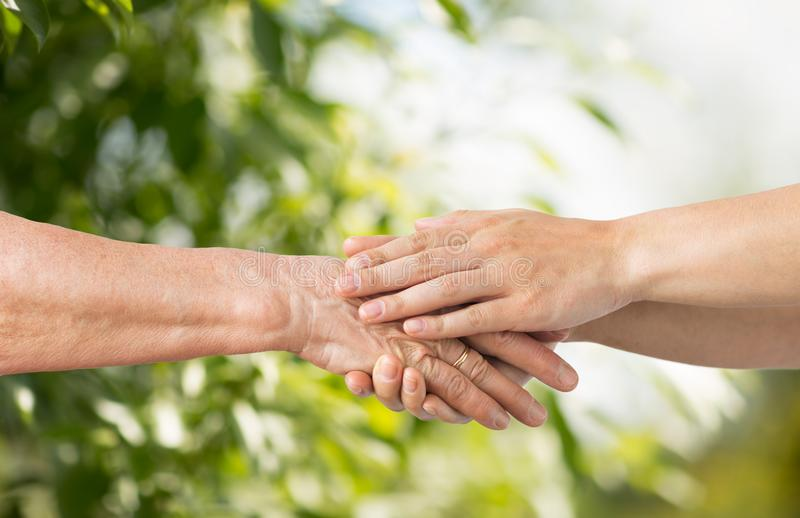 Close up of senior and young woman holding hands. People, age and charity concept - close up of senior and young woman holding hands over green natural royalty free stock photo