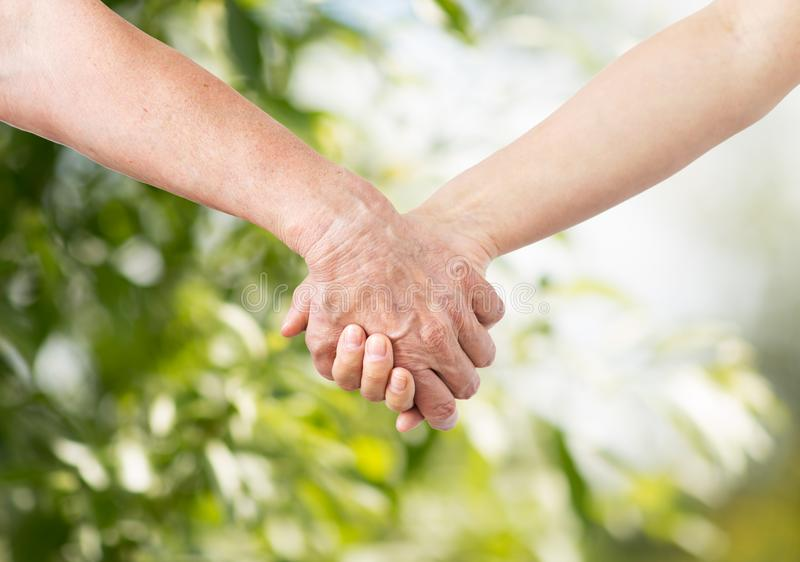 Close up of senior and young woman holding hands. People, age and charity concept - close up of senior and young woman holding hands over green natural stock image