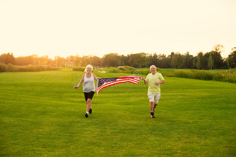 People with American flag running. royalty free stock images