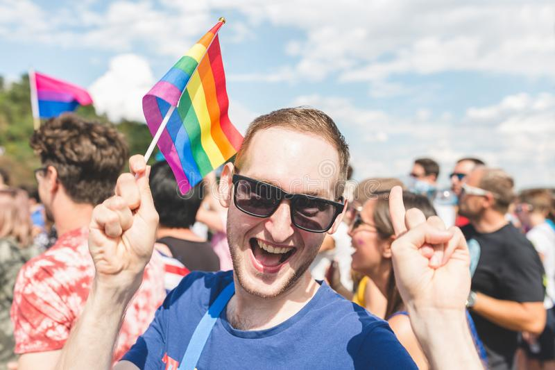 People at the annual Prague Gay Pride parade. Man with a rainbow flag, smiling. Prague, Czech Republic - August 11, 2018: Participants of the annual Prague Gay royalty free stock image