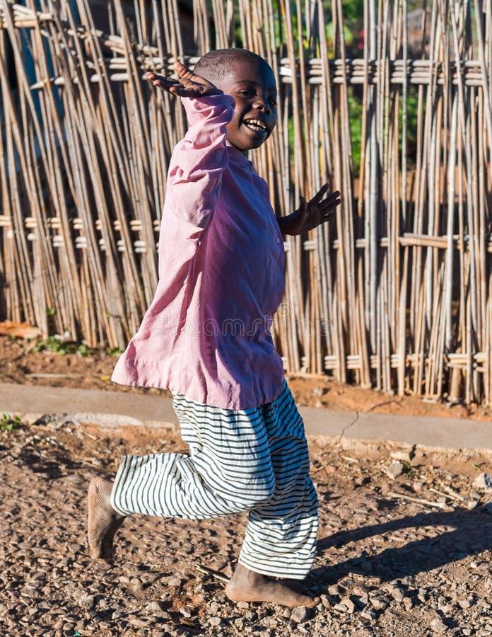 People in ANTANANARIVO, MADAGASCAR. ANTANANARIVO, MADAGASCAR - JULY 3, 2011: Unidentified Madagascar boy runs happily in the street. People in Madagascar suffer royalty free stock image