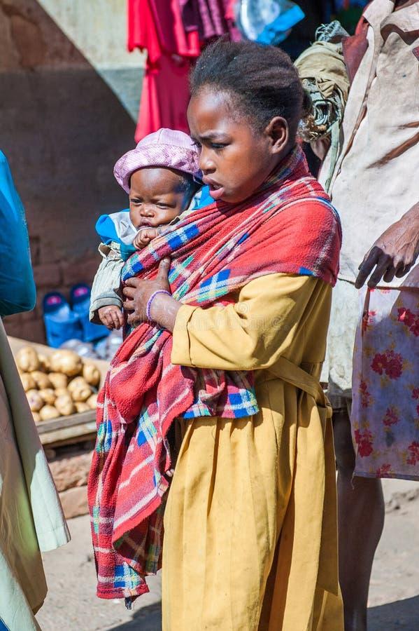 People in ANTANANARIVO, MADAGASCAR. ANTANANARIVO, MADAGASCAR - JUNE 30, 2011: Unidentified Madagascar woman holds her little baby. People in Madagascar suffer of stock photos