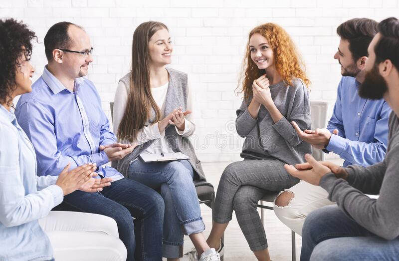 People applauding to young woman at therapy session in rehab royalty free stock photography