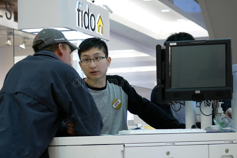 People asking fido sales clerk about cellphone plan. Inside Burnaby shopping mall stock photography
