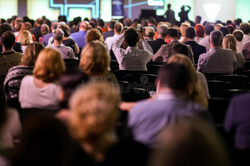People attend a conference in a big hall stock photography