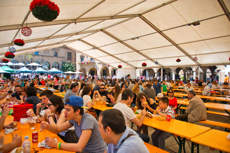 People attending an Oktoberfest in Spain. People attending an Oktoberfest in a covered marquis in Barcelona, Spain in proper Bavarian tradition with beer and stock image