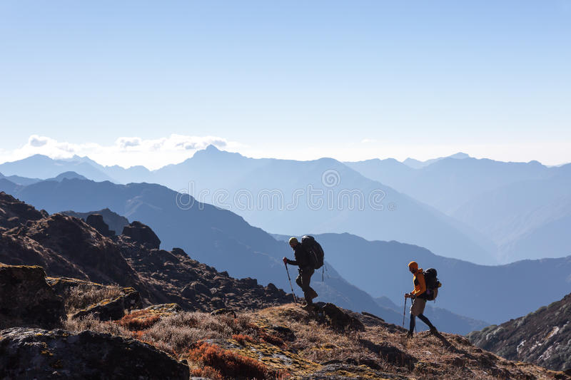 People with Backpacks and trekking Sticks traveling in Mountains stock images