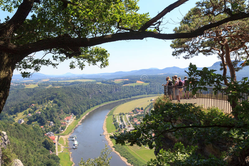 People on Bastei rocks looking at panorama with river Elbe and Rathen, Saxon Switzerland royalty free stock image
