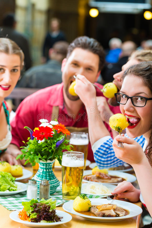 People in bavarian Tracht eating in restaurant or pub. Young people in traditional Bavarian Tracht eating pork in restaurant or pub for lunch or dinner stock image