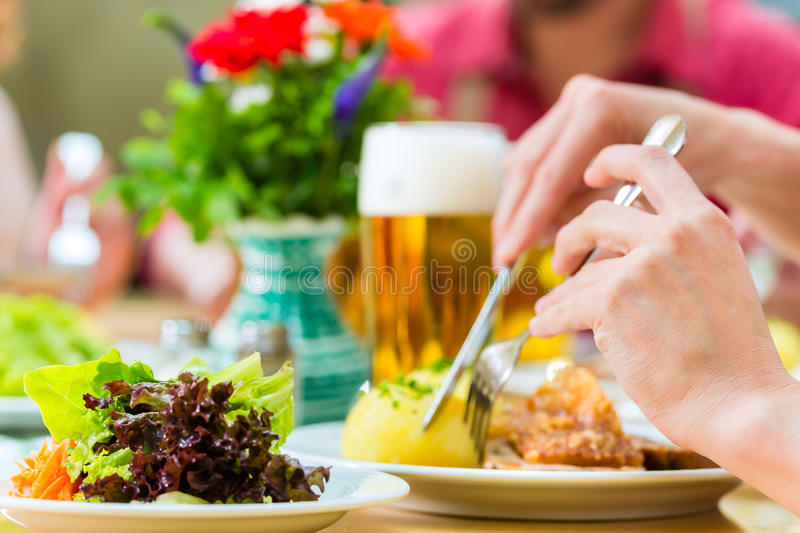 People in bavarian Tracht eating in restaurant or pub. Young people in traditional Bavarian Tracht eating pork in restaurant or pub for lunch or dinner royalty free stock images