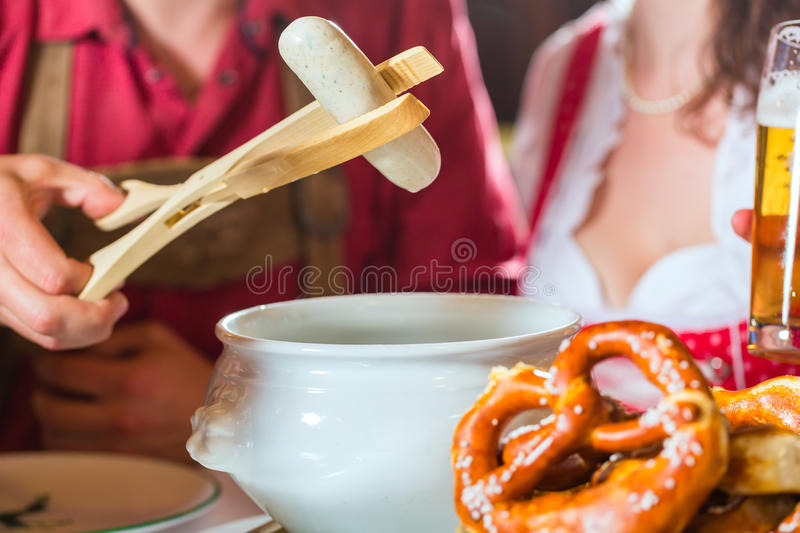 People in Bavarian Tracht eating in restaurant or pub. Young people in traditional Bavarian Tracht eating with sausages in restaurant or pub lunch or dinner royalty free stock images
