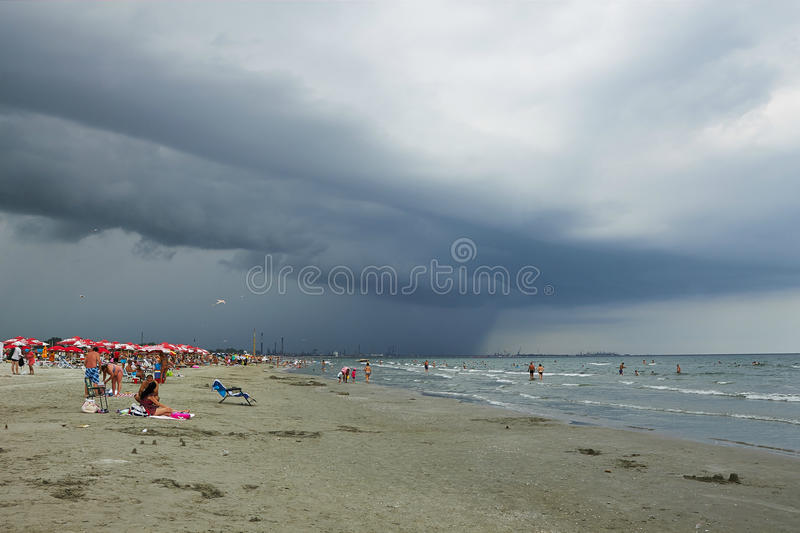 People at the beach and dark clouds. People at the beach on August 15,2014 in resort Navodari, Romania. The storm was coming at the Black Sea royalty free stock image