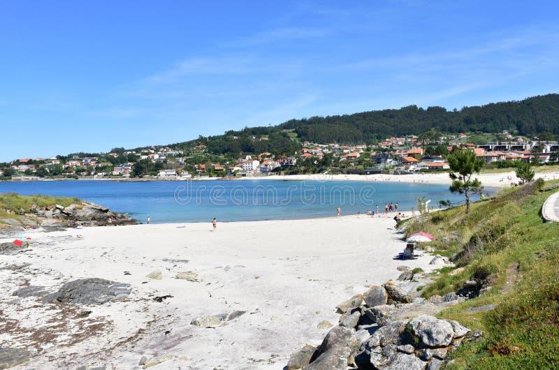 People on the beach, bay with blue water. Areas Beach, Rias Baixas, Pontevedra Province. Sanxenxo, Spain. stock photo