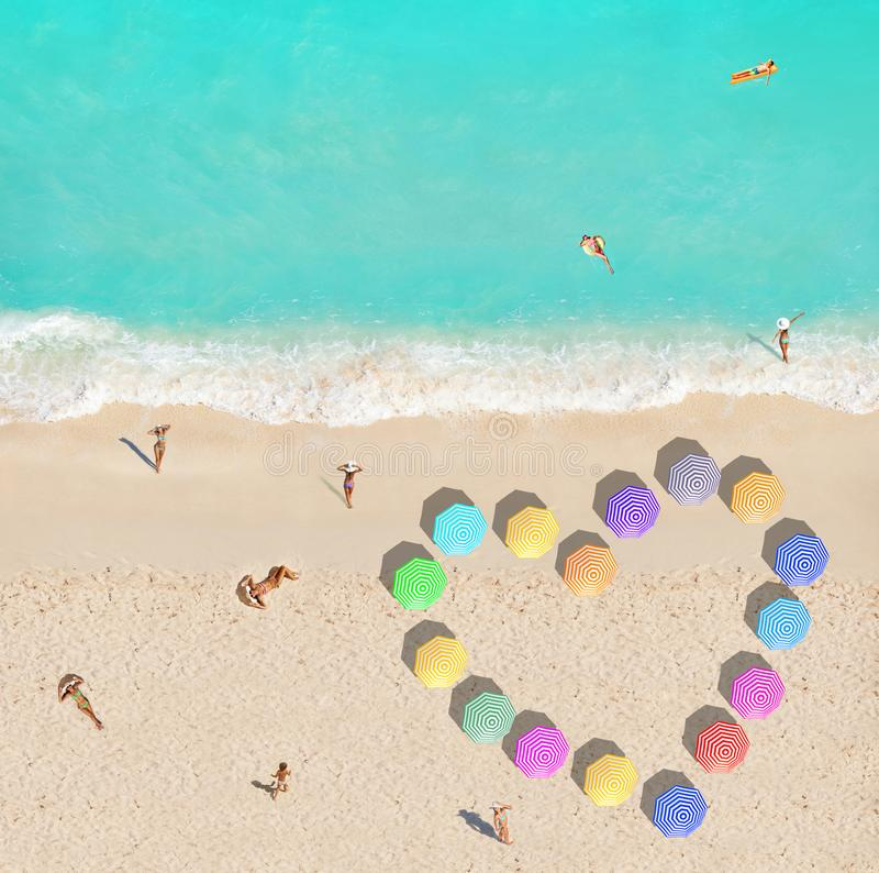 People on beach and heart shape made of umbrellas stock photos