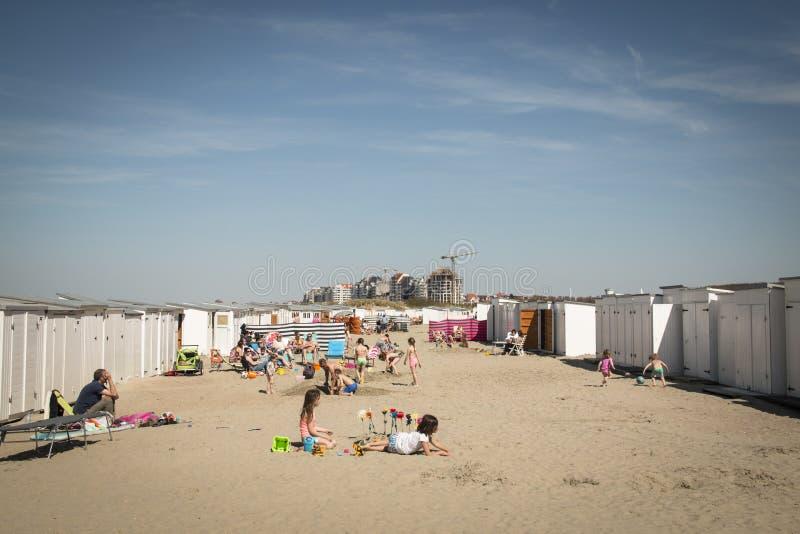 People on the beach in Knokke, Belgium. KNOKKE, BELGIUM - MAY 2016: People on the beach surrounded by the typical cabins in Knokke, Belgium royalty free stock photo