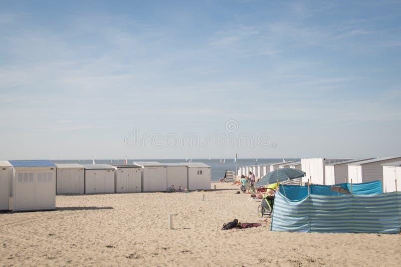 People on the beach in Knokke, Belgium. KNOKKE, BELGIUM - MAY 2016: People on the beach surrounded by the typical cabins in Knokke, Belgium stock photos