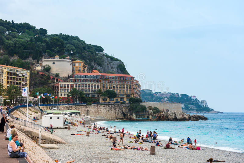 People on the beach of the mediterranean sea in Nice. FRANCE, NICE - JUNE 13: people on the beach of the Mediterranean sea. Cote d Azur, Nice, France on June 13 stock photos