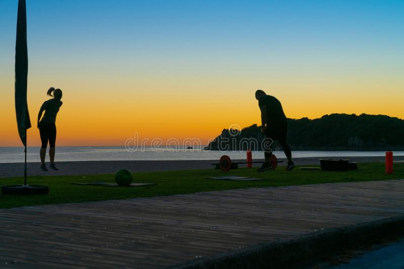 People on beach at Mount Maunganui at sunrise in silhouette doing morning fitnes exercise and walking by stock photography