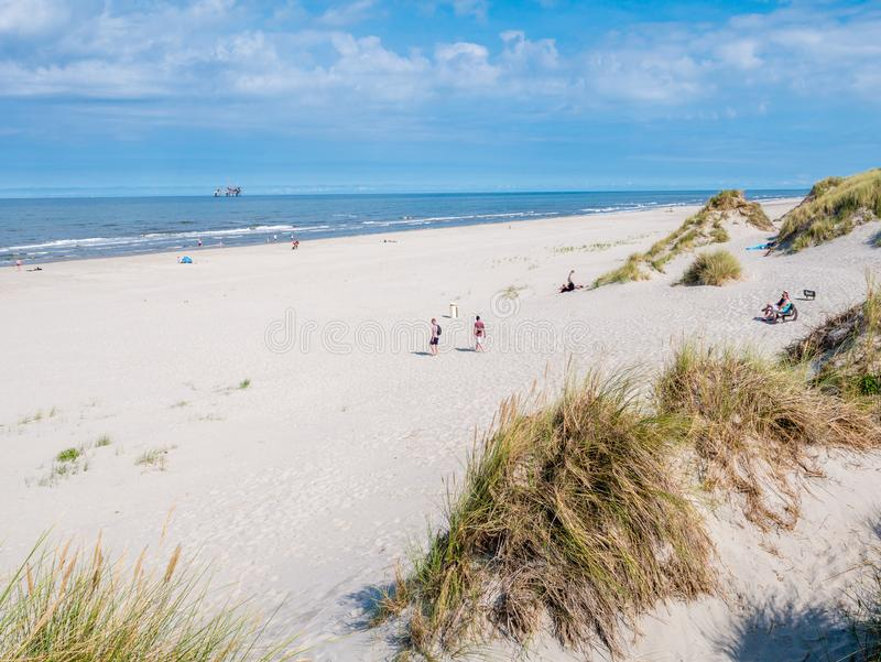 People on beach and North Sea with offshore platform, West Frisian island Ameland, Friesland, Netherlands. People on beach and North Sea with offshore drilling stock photos