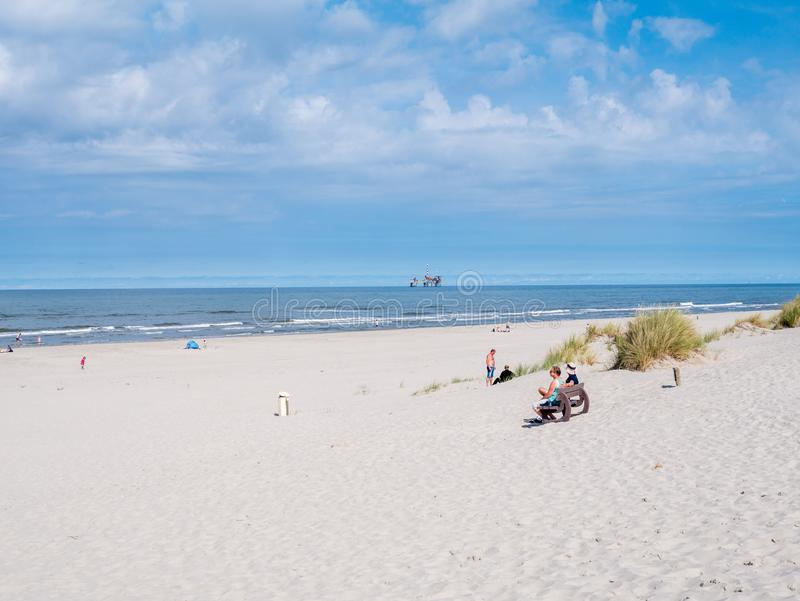 People on beach and North Sea with offshore platform, West Frisian island Ameland, Friesland, Netherlands. People on beach and North Sea with offshore drilling royalty free stock image