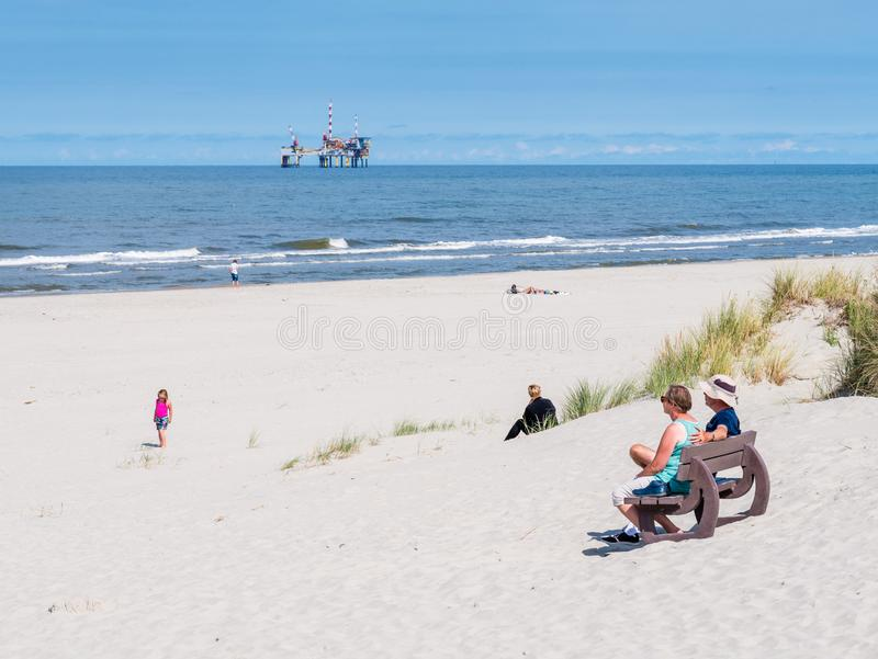 People on beach and North Sea with offshore platform, West Frisian island Ameland, Friesland, Netherlands. People on beach and North Sea with offshore drilling stock images