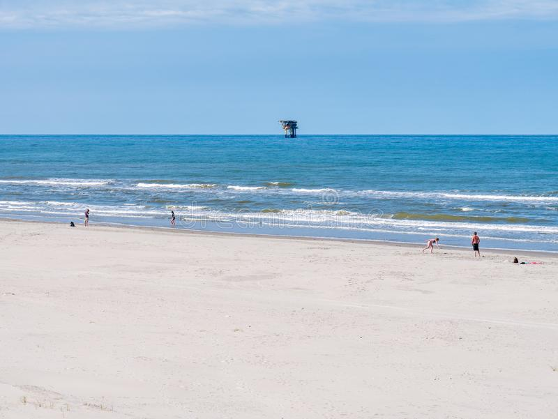 People on beach and North Sea with offshore platform, West Frisian island Ameland, Friesland, Netherlands. People playing on beach and North Sea with offshore royalty free stock images