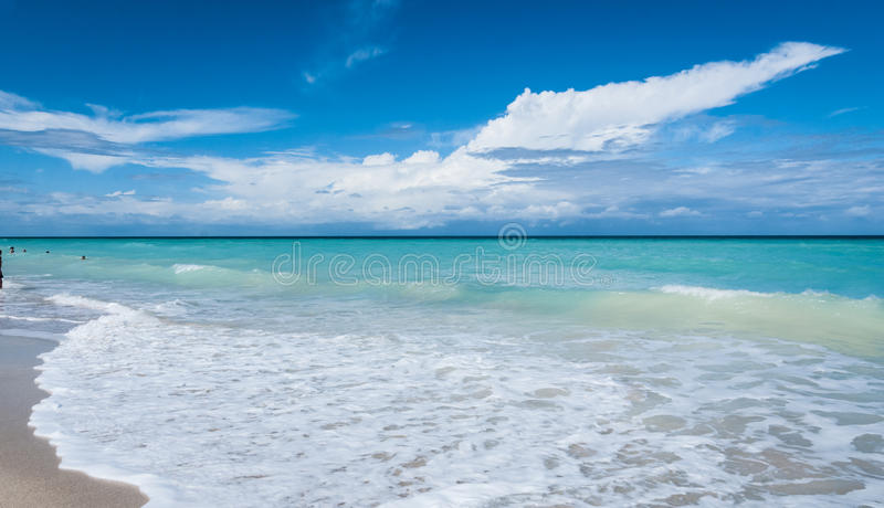 People on a beach relaxing on holidays, resort beaches, cloudscape on horizon. Travel and beach holidays. Warm ocean waves gently lap against a Cuban beach royalty free stock photos