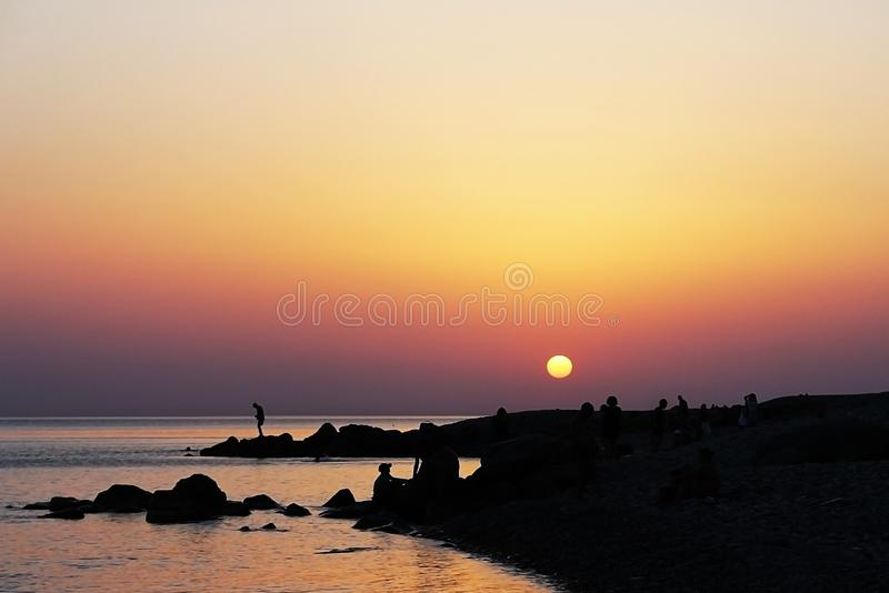 People on the beach in sunset light. Silhouettes of people on the beach in sunset light stock photos