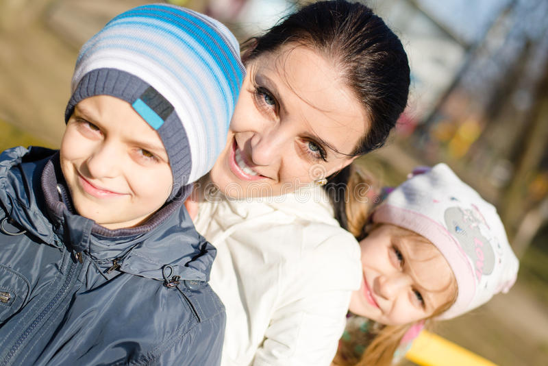 3 people beautiful young mother with two children, son and daughter having fun happy smiling & looking at camera, closeup portrait stock photos