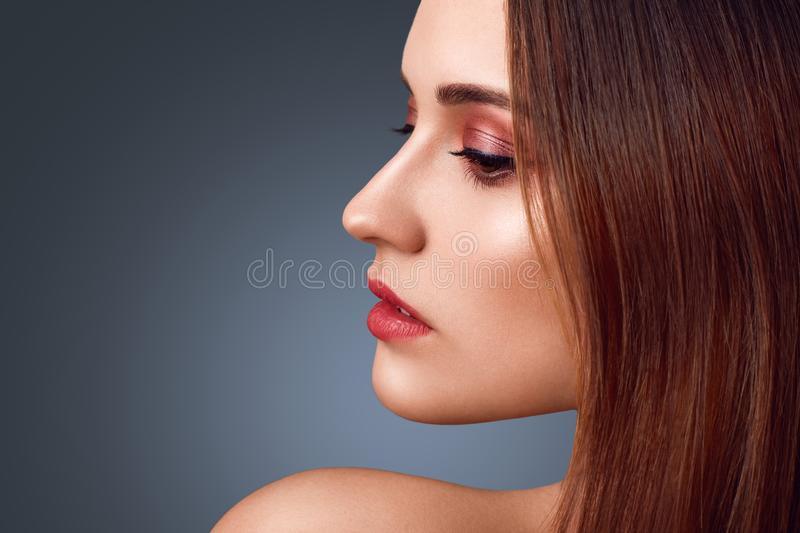 People, beauty concept. Sideways portrait of nude brunette female with wonderful make up, red painted lips, healthy pure skin, pos. Es against dark studio stock image