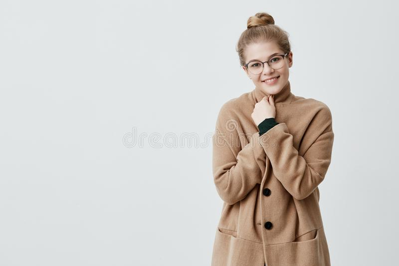 People, beauty and lifestyle. Sensual woman with wide smile dressed in brown coat smiling broadly being happy to meet stock photos