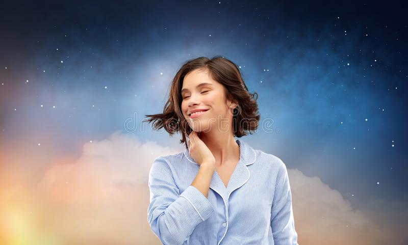 Happy woman in pajama over night sky background royalty free stock image