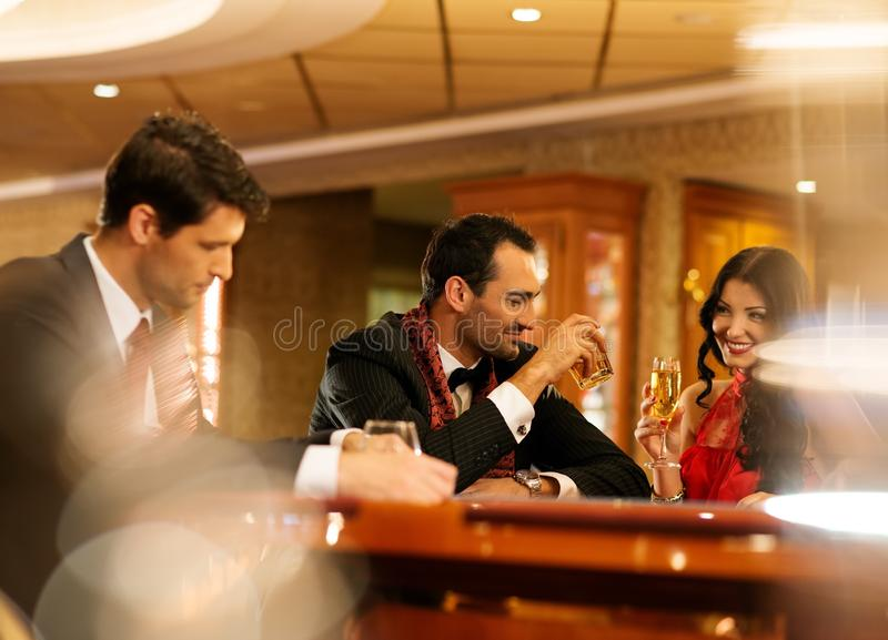 People behind gambling table stock photo