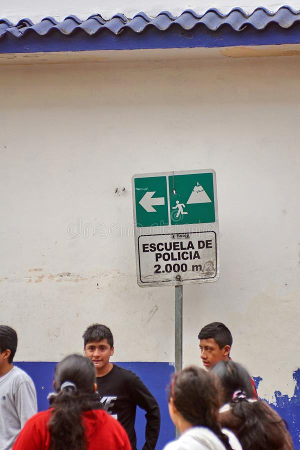 People below an evacuation sign. Crowd on people on the sidwalk below a volcanic eruption evacuation route sign in Banos, Ecuador royalty free stock images