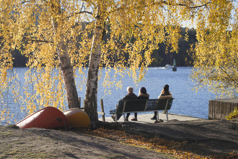 People on bench by water, framed in beautiful autumn colors. Three persons sitting on a bench by the water in Stockholm, Sweden, on a beautiful fall day. They royalty free stock photos