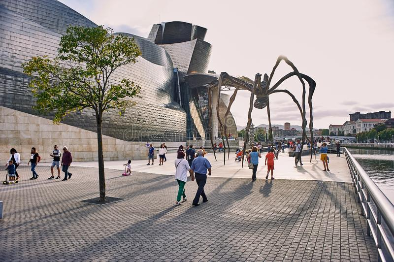 People walking around the Guggenheim museum. Spain. The people of Bilbao take advantage of the good summer weather to walk around the museum and contemplate royalty free stock photography