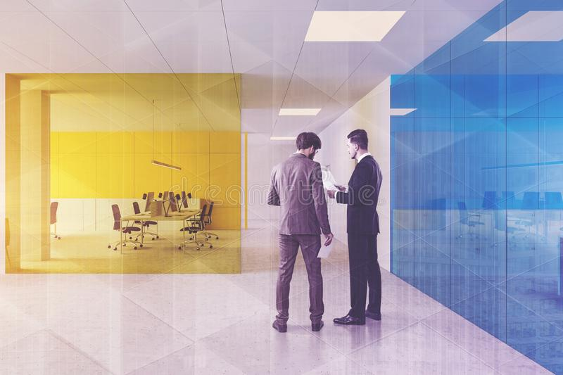 People in blue and yellow office stock image
